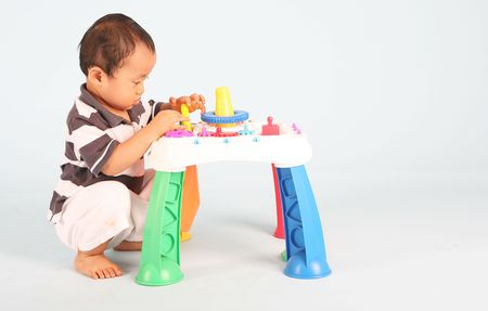 An Unhappy asian toddler playing with his toy alone Stock Photo - 3438779