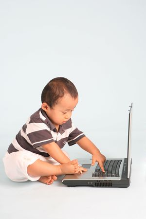 A serious toddler using a laptop computer. Stock Photo - 3438786