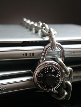 Two laptop computers with chain and combination lock photo