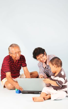 grandmother and grandson: Learn how to use a laptop computer with grandpa & grandma Stock Photo
