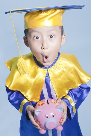 scholar: Scholar dressed toddler with piggy bank making a funny face Stock Photo