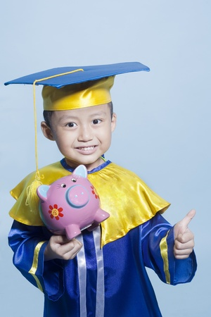scholar: Scholar dressed toddler carrying piggy bank