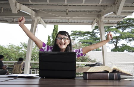 Excited asian woman with laptop photo
