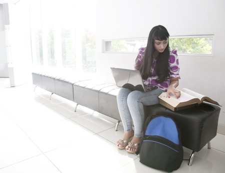 Beautiful Asian student working with laptop and books photo