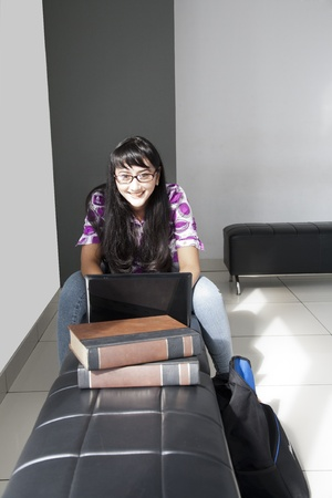 Beautiful Asian student smiling whie working on her assignment  photo
