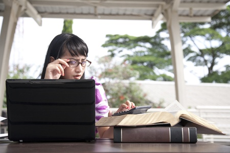 Young asian business woman with glasses working outdoor photo