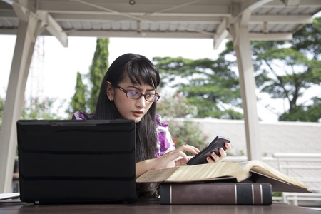Young asian woman with glasses working on her laptop outdoor photo