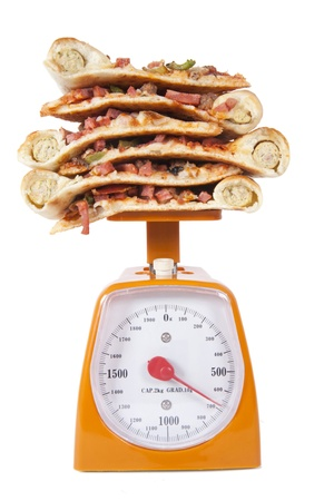 Photo of pizza slices stacked on a scale isolated over white photo