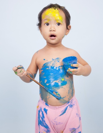 Cute little girl playing with her paint and brush shot in studio photo