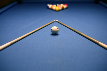 cues: Billiard blue table with balsl and cues in beginning position.