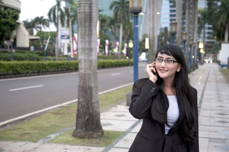 adult indonesia: businesswoman making a phone call on the street