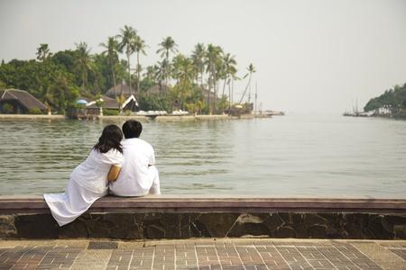 honeymooner: Reci�n casado asiento junto a la playa, mirando en el complejo Foto de archivo