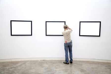 a Museum worker arranging frames on the wall  photo