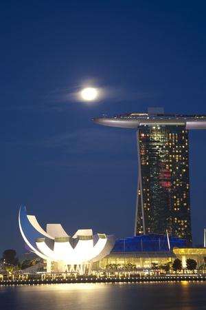 marina: Night shot of moon over Marina Bay Sands Hotel and Integrated Resort, and the Singapore Arts and Science Museum.