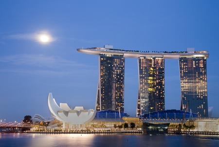 marina bay: Night shot of moon over Marina Bay Sands Hotel and Integrated Resort, The Helix Bridge, and the Singapore Arts and Science Museum.