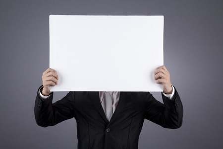 Businessman holding a blank sign shot in studio photo