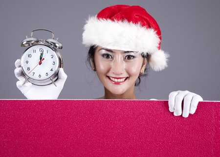 Beautiful woman with holding an alarm clock and a red blank sign photo