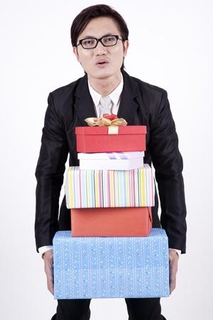 dar un regalo: Hombre de negocios inteligente con gafas de llevar regalos pesados Foto de archivo