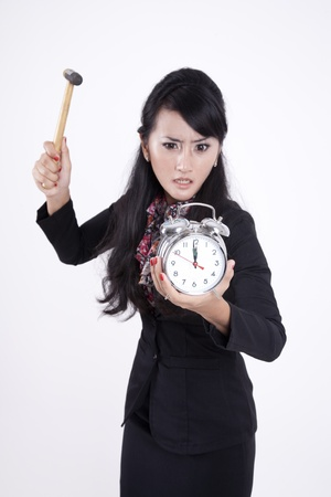 Business woman smashing alarm clock with hammer photo