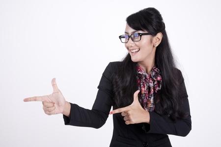 Smiling Asian businesswoman gesturing shot in studio photo