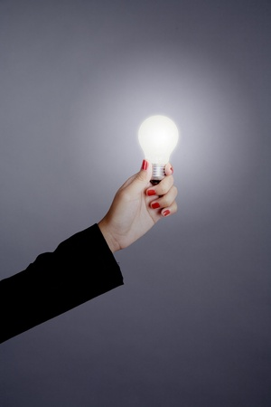 Businesswoman hand holding a light bulb isolated on grey photo