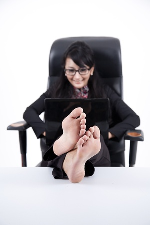 Businesswoman using laptop with Feet Up on a Table  isolated on white Stock Photo - 11077690