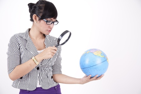 Asian woman using magnifying glass  to search the globe Stock Photo - 11077719