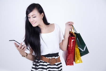 Beautiful woman smiling with her digital tablet and shopping bags photo