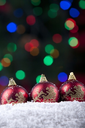 Christmas balls shot on snow with colorful lights in background Stock Photo - 11204401