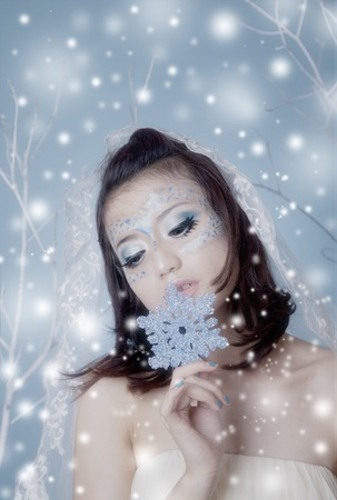 Conceptual portrait of snow queen holding a snowflake photo