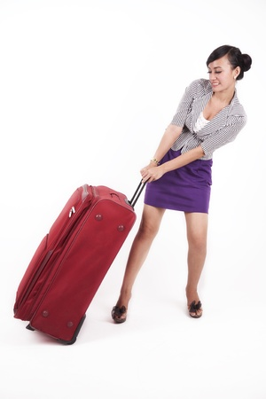 Asian woman pulling a heavy suitcase isolated on white photo