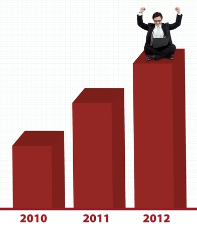 Happy Asian businessman with laptop sitting on 2012 bar chart photo