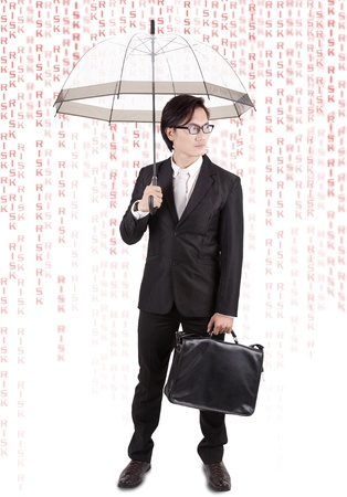Asian businessman with umbrella and the word risk pouring down like rain photo