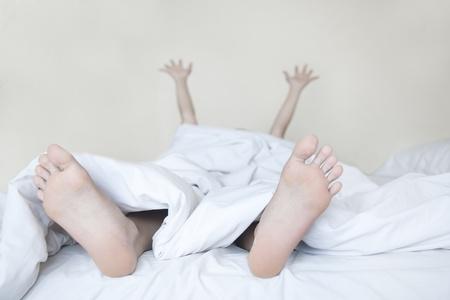 Woman Aufwachen im weißen Bett Streching Arme und Beine