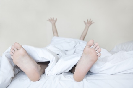 young girl feet: Woman waking up in white bed streching arms and legs