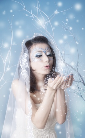 Conceptual portrait of winter queen blowing kisses during snowstorm