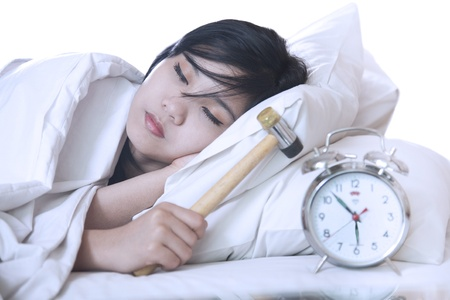 against the clock: Alarm clock against the sleeping girl with a hammer in a hand  Stock Photo