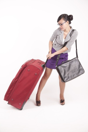 Asian business woman pulling a heavy suitcase isolated on white photo