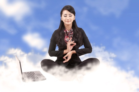 Business woman with laptop meditating sitting on clouds photo