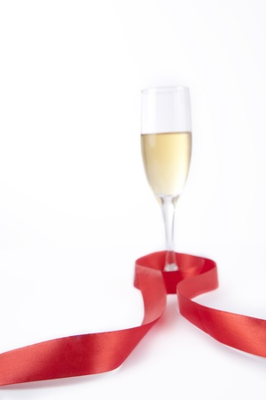 Glass of champagne with ribbon isolated on white photo