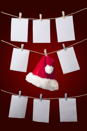 clothes pegs: Santa hat with empty notes hanging over red background