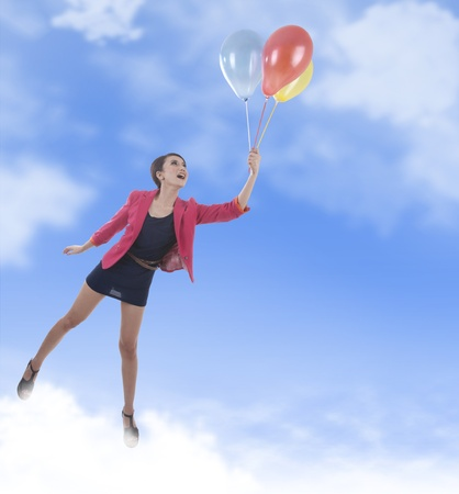 Happy business woman flying with colorful balloon photo