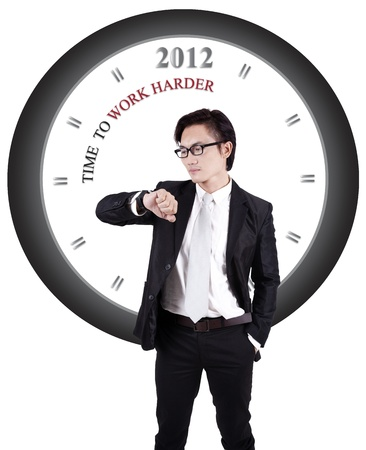Asian businessman with a big clock with writing: time to work harder photo