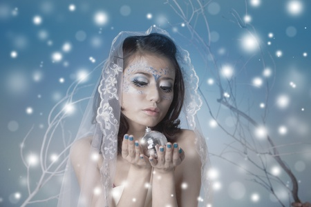 Winter concept showing beautiful woman with disco ball photo