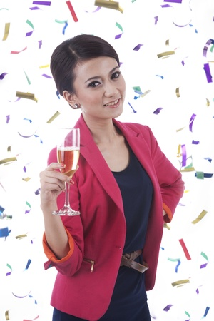 Woman with glass of champagne and confetti around her photo