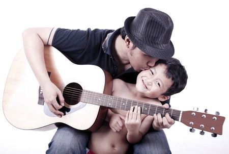 Musician father kisses his son while holding a guitar isolated on white photo