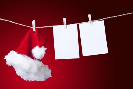 Santa hat with blank notes hanging over red background photo