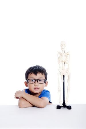 science class: Smart Asian boy with glasses and human skeleton model isolated on white