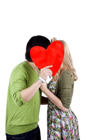 Mix race couple kissing while hiding behind a red heart photo