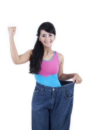 Happy Asian woman shows her old huge pair of jeans. Weight loss concept, shot in studio photo